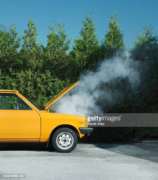 Yellow car with steam pouring from bonnet