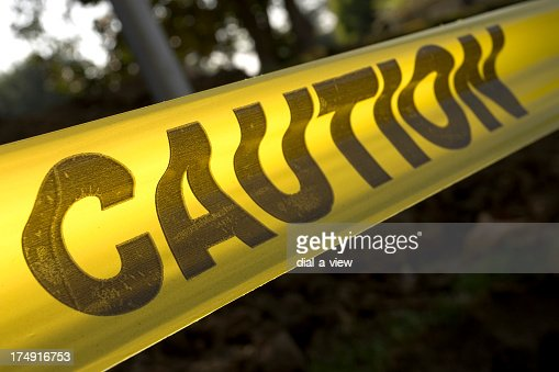 Yellow caution tape stretched across an exterior background