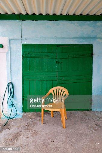 Amarelo cadeiras na frente da porta verde : Foto de stock