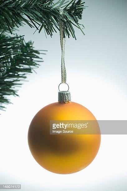 Yellow christmas bauble hanging on tree