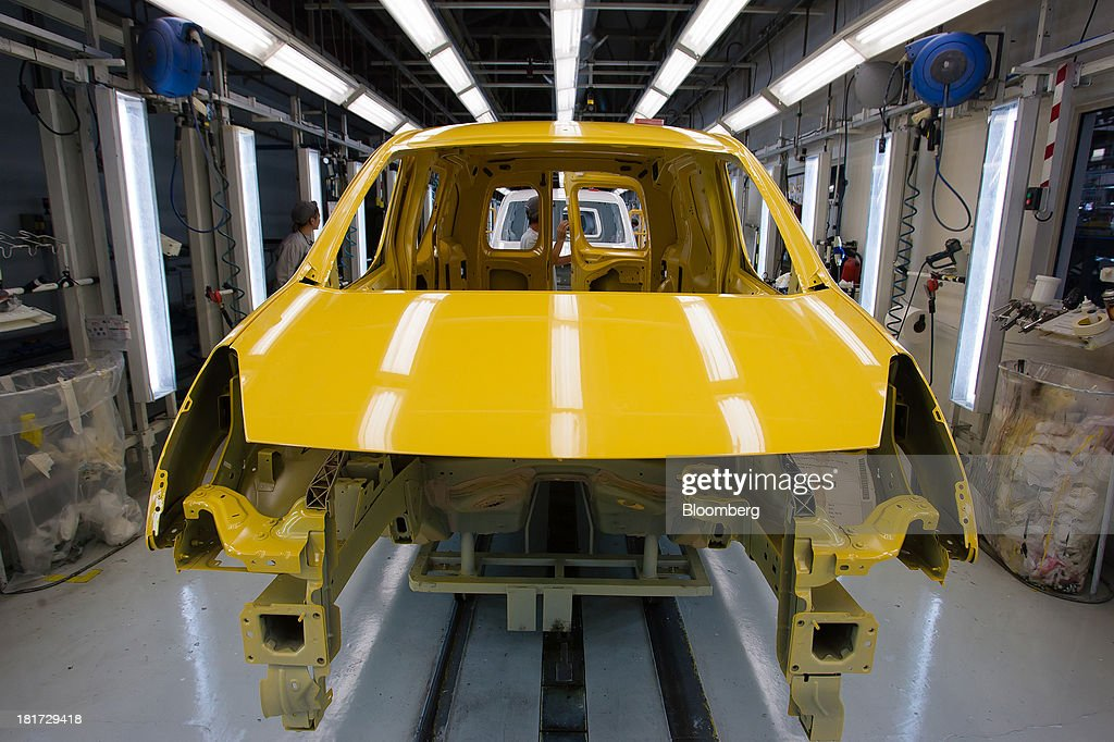 A yellow Citroen Berlingo automobile body shell moves along the production line at the PSA Peugeot Citroen plant in Mangualde, Portugal, on Monday, Sept. 23, 2013. Some economists point to falling labor costs across southern Europe as a sign the region may be becoming more attractive as a manufacturing base. Photographer: Mario Proenca/Bloomberg via Getty Images