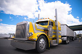The classic yellow powerful American heavy big rig semi truck with chrome accents and individually designed customized truck body moving in a truck stop parking lot with two bulk trailers on backgroun