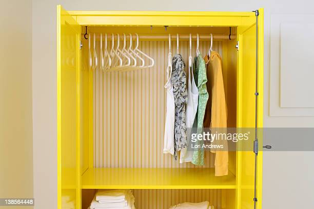 Yellow closet with doors open and hangers