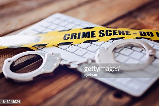 Yellow crime scene tape and handcuffs on computer keyboard. : Stock Photo