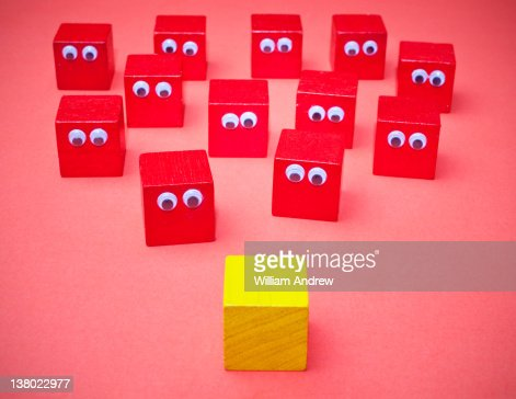 Yellow cube meets red cubes : Stock Photo