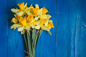 Yellow daffodils bouquet on blue wooden background, easter card. Place for text.Flowers background