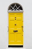 front view of yellow elegant residential apartment door with glass window and metallic vintage mailbox