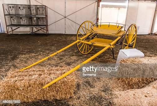 Yellow empty carriage sits near hay bales : Stock Photo