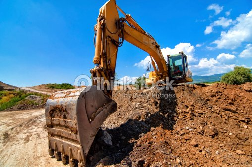 Construction Site Soil : Yellow excavator moving soil and sand on construction site