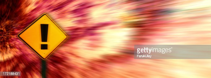 Yellow exclamation point warning sign on blurred background