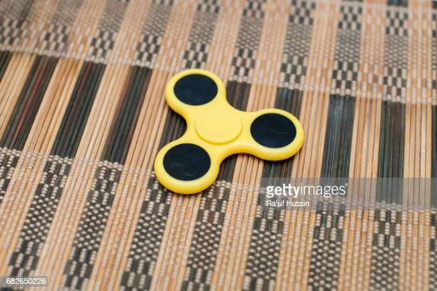 Yellow fidget spinner stress relieving toy on liner of wood