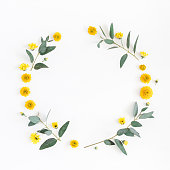 Flowers composition. Wreath made of various yellow flowers and eucalyptus branches on white background. Flat lay, top view, copy space, square