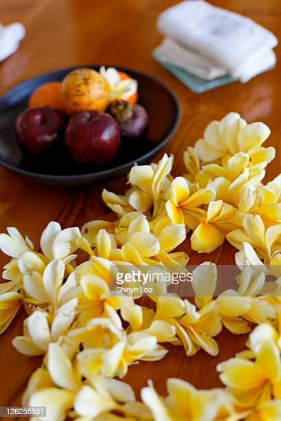 Yellow flowers with fruits in plate on table