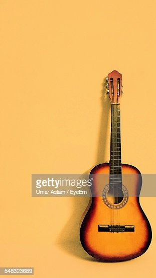 Yellow Guitar Against Yellow Background