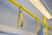 Yellow hand grip straps inside subway train, selective focus on front object