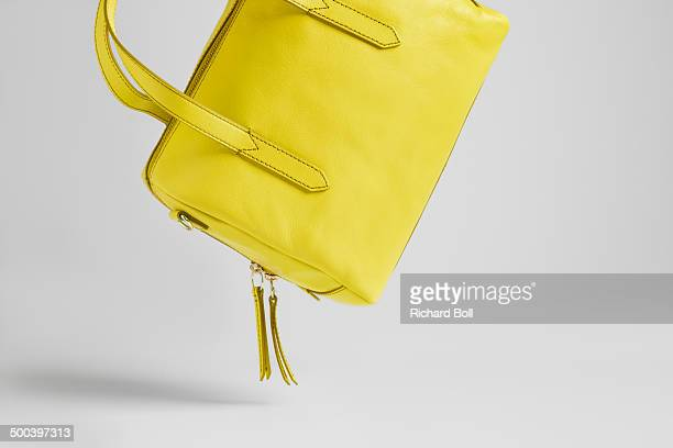 Yellow handbag falling on to a white background