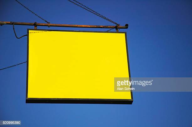 Yellow hanging sign and sky