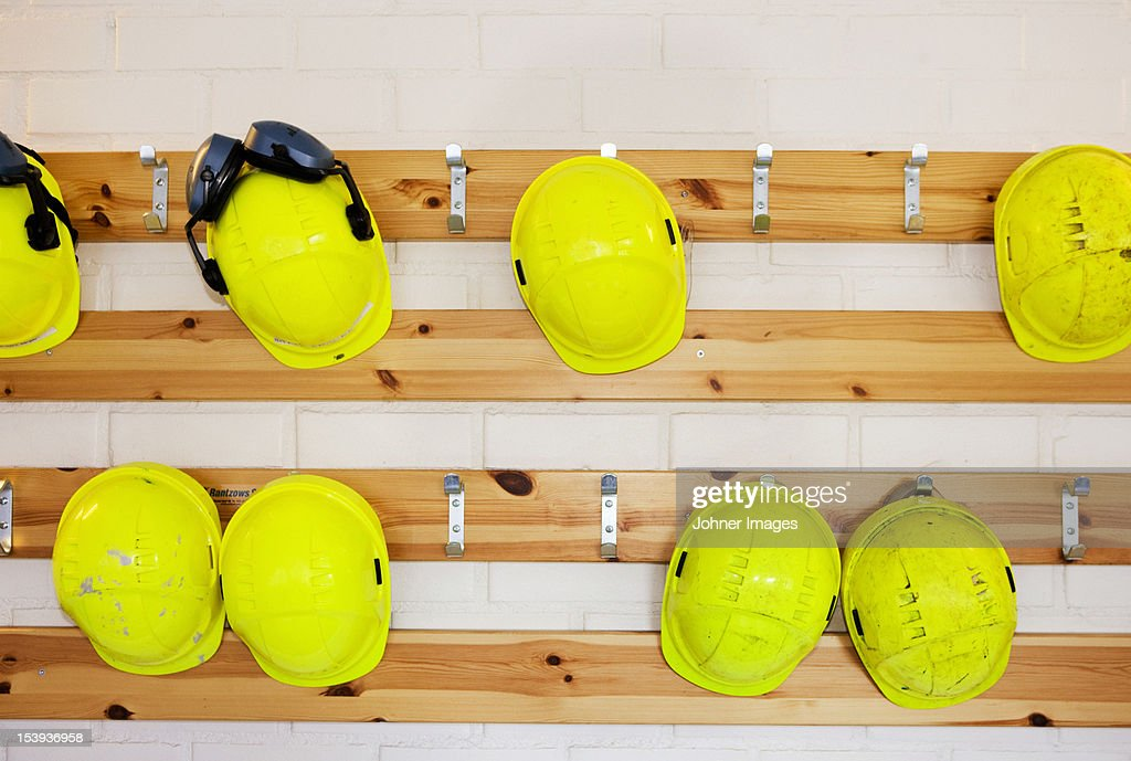 Yellow hard hats hanging on rack