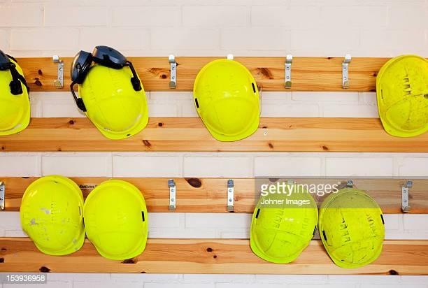 Yellow hard hats hanging on rack