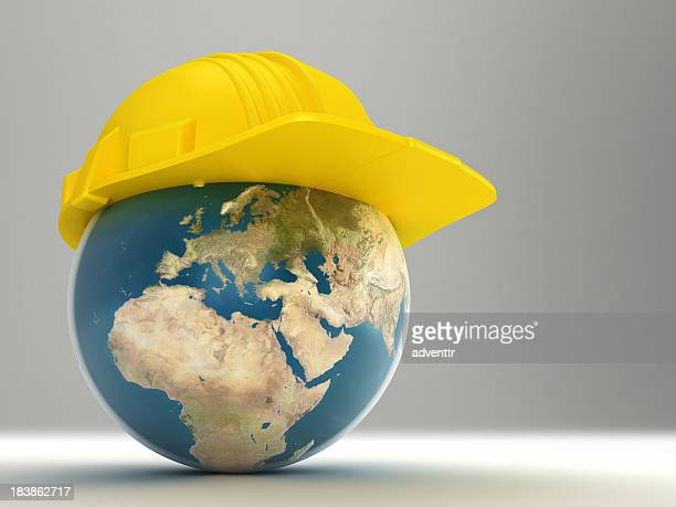 Yellow hardhat on top of digital image of Earth