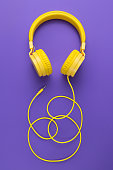 Yellow headphones on purple background. Music concept