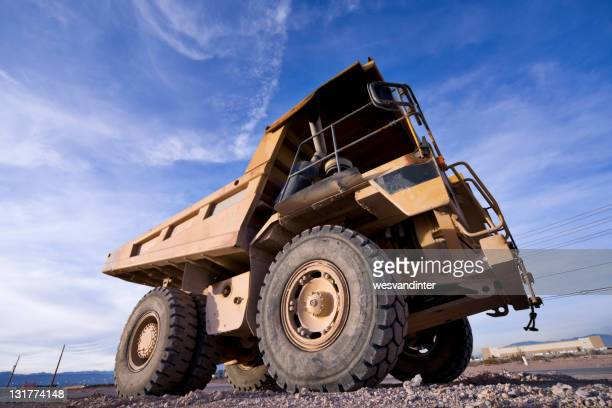 Yellow heavy equipment dump truck as seen from the ground
