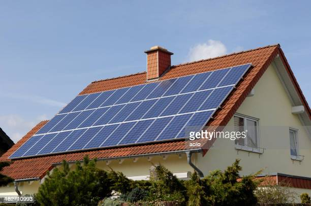 Gelbe Haus mit Solarzellen auf dem Dach