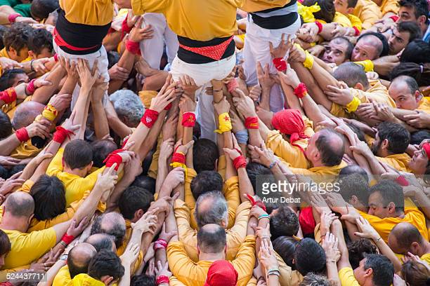 Yellow human tower 'Castellers' view from above.