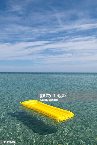 A yellow inflatable raft floating on the sea, Budoni, Sardinia, Italy