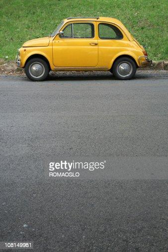 Yellow Italian vintage car in Rome : Stock Photo