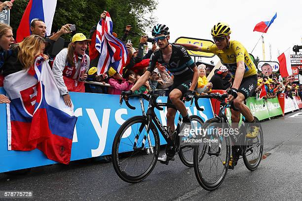 Yellow Jersey leader Chris Froome of Great Britain and Team Sky is helped to the finish line by team mate Wout Poels at the end of the 146 km...