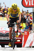 Yellow Jersey leader Chris Froome of Great Britain and Team Sky crosses the finish line with cuts ripped clothing and riding the bike of team mate...
