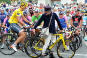 Yellow jersey of Overall Leader Switzerland's Fabian Cancellara rides with a postman performer's old bike as Green jersey of Best Sprinter Norway's...