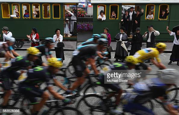 Yellow jersey race leader Chris Froome of Team Sky passes by a steam train with supporters dressed in old style costumes during the 1465km stage...