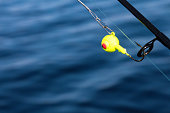 Image of a yellow jig head with a red eye.  The hook of the tackle is hooked on an eye of the fishing pole.  Behind the bright tackle is blurry bright blue water.  This type of jig is used while fishi