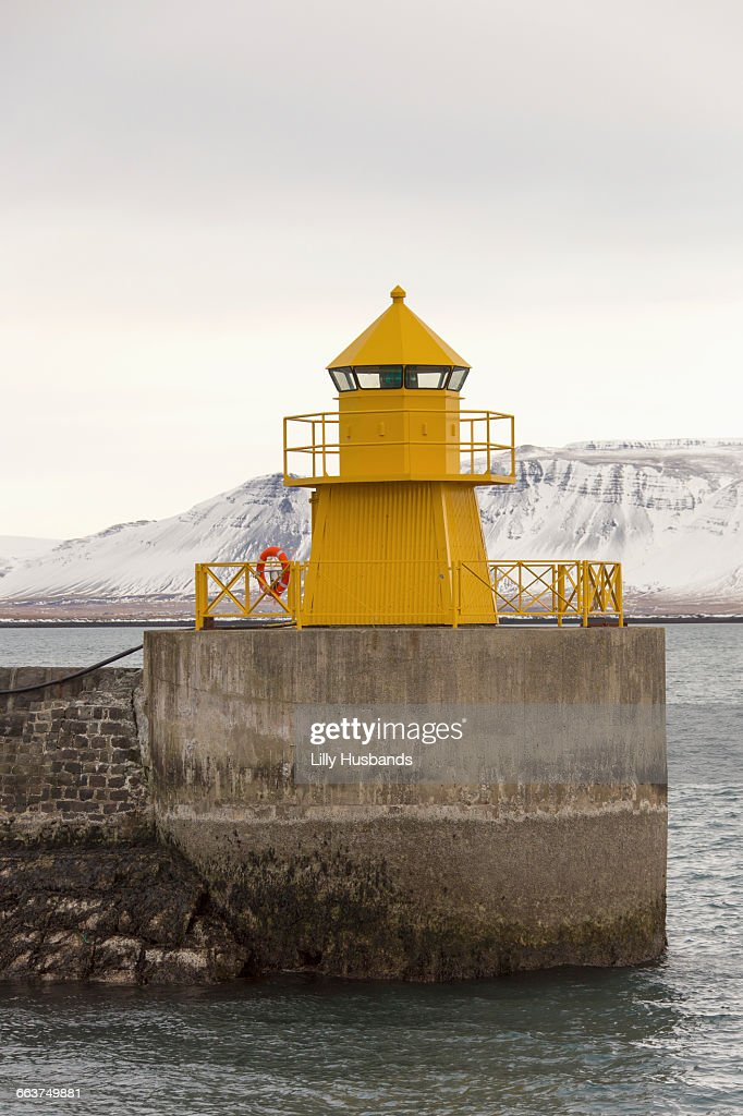 Yellow lighthouse in sea against sky