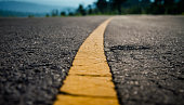 Asphalt highway with yellow line detail on road background