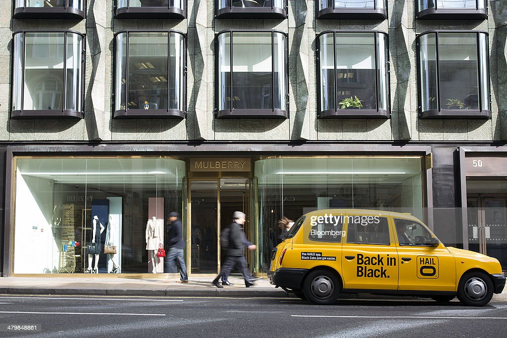 A yellow London taxi cab operated by Hailo Network Ltd. stands outside a Mulberry Group Plc luxury store on New Bond Street in London, U.K., on Thursday, March 20, 2014. Mulberry Group said Bruno Guillon will step down as chief executive officer after two years during which the British luxury handbag maker lost two-thirds of its market value. Photographer: Simon Dawson/Bloomberg via Getty Images
