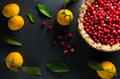 Yellow mandarins with leaves and cranberries in a basket on a gray stone free space horizontal