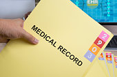 Yellow medical record folder in someone hand.