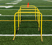A close up of four yellow mini hurdles with orange cones behind them on a green turf field.