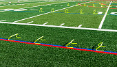 Six and twelve inch yellow mini hurdles are set up on a green turf field for speed and agility practice.