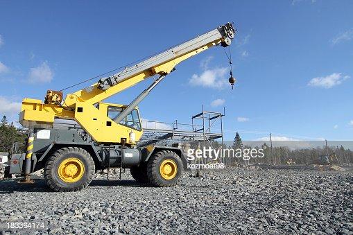 Yellow mobile construction crane driving over gray gravel