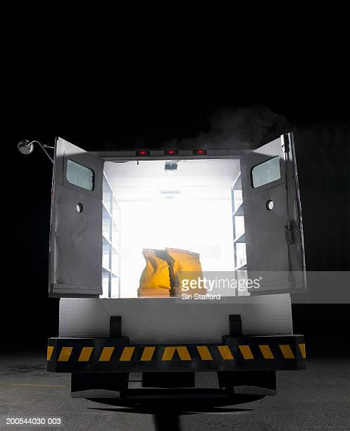 Yellow money bags sitting in open rear doors of armored truck