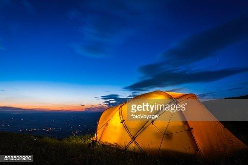 Yellow mountain tent illuminated at dusk on summer mountain ridge