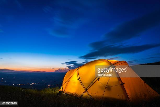 Yellow mountain tent illuminated at dusk on summer mountain ridge