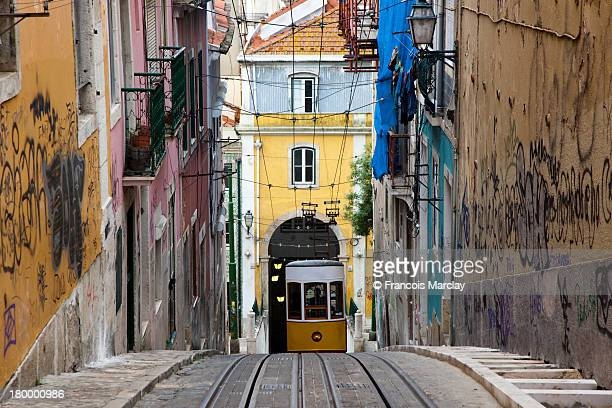 Yellow old tram going up hill in Lisbon