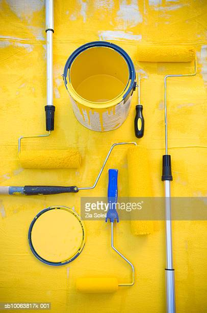 Yellow paint, buckets, rollers, brush and drop cloth, overhead view
