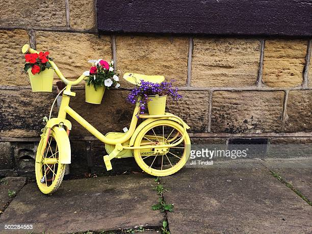 Yellow painted bicycle displayed outside traditional Yorkshire stone building to welcome the Tour de France 2014