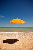 Yellow parasol casting shadow on beach